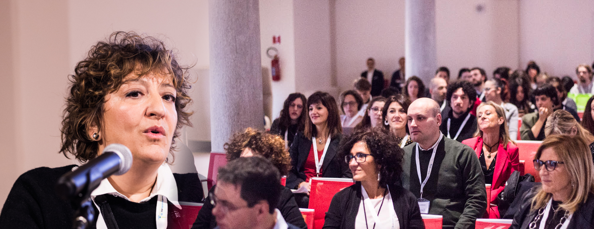 Picture of speaker Antonella Toffetti cut onto a picture of the audience that is listening to her.